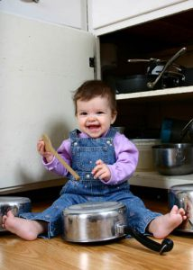 Adorable baby girl banging on pots and pans with a wooden spoon in the kitchen.