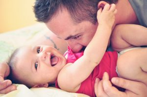 Father playing with his little happy and smiling baby daughter